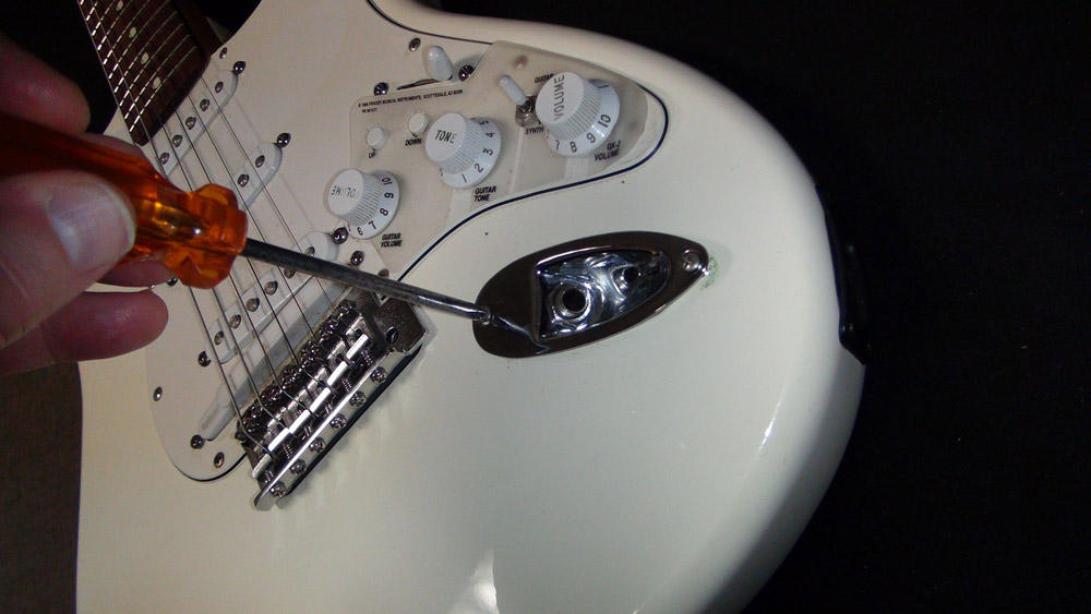 Tighten the screws that hold the plate to the guitar.